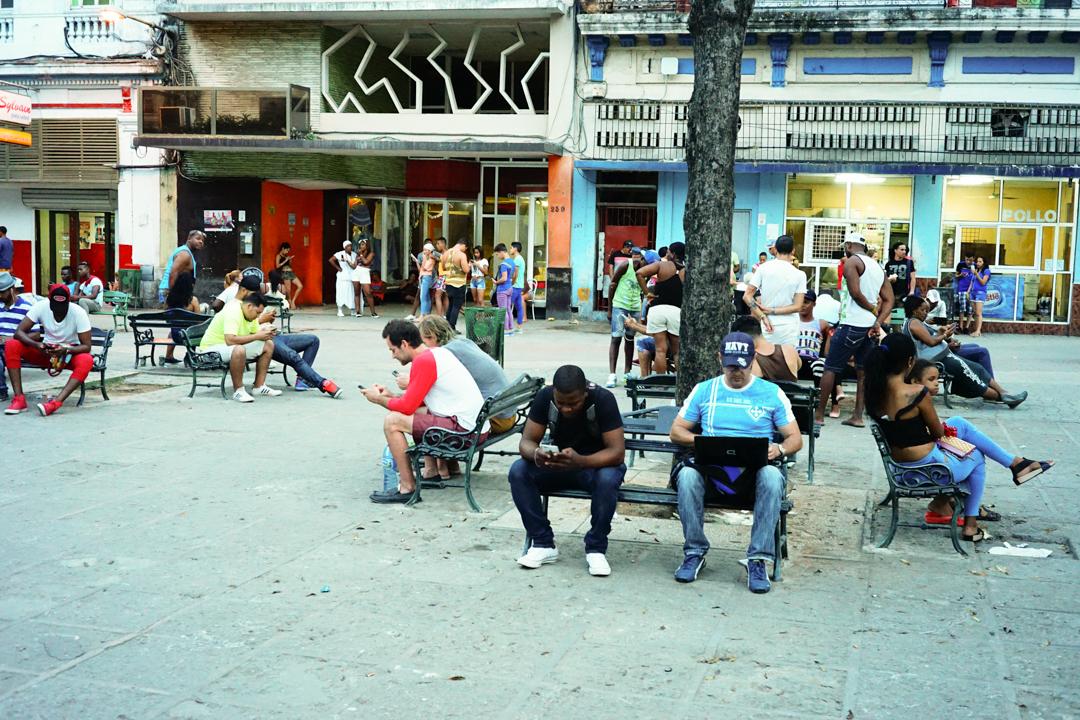 広場でノートPCやスマホでネットをする人々