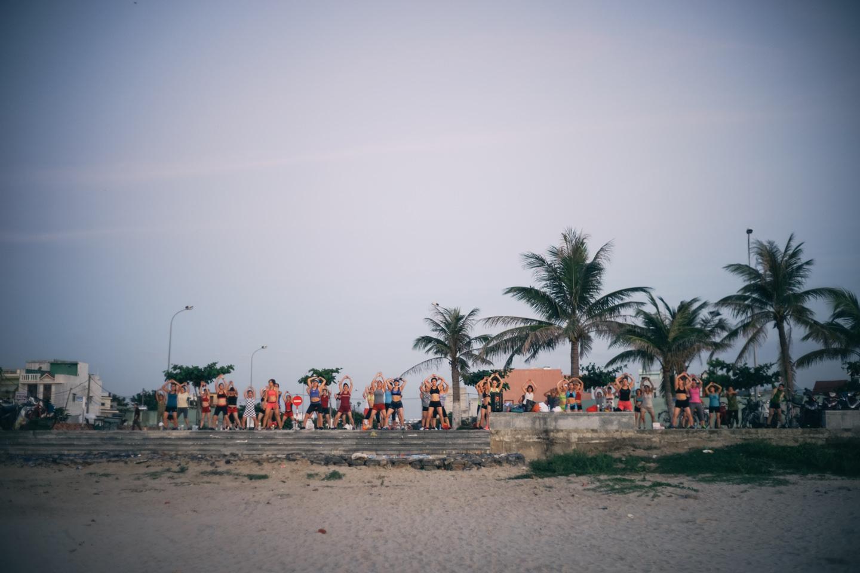 朝ビーチ沿いで体操に励む人々